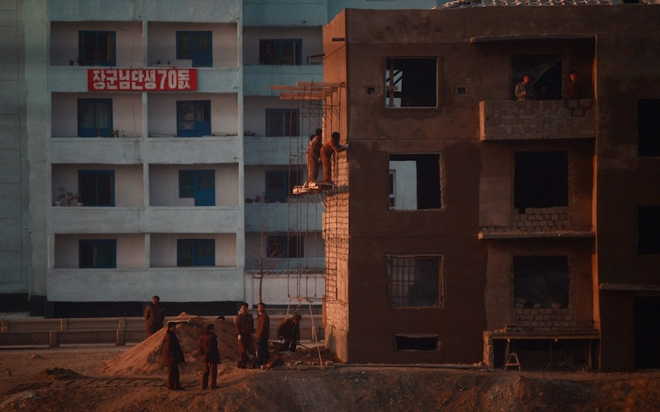 North Korean workers are seen from the window of a train as they work on a construction site along the railway