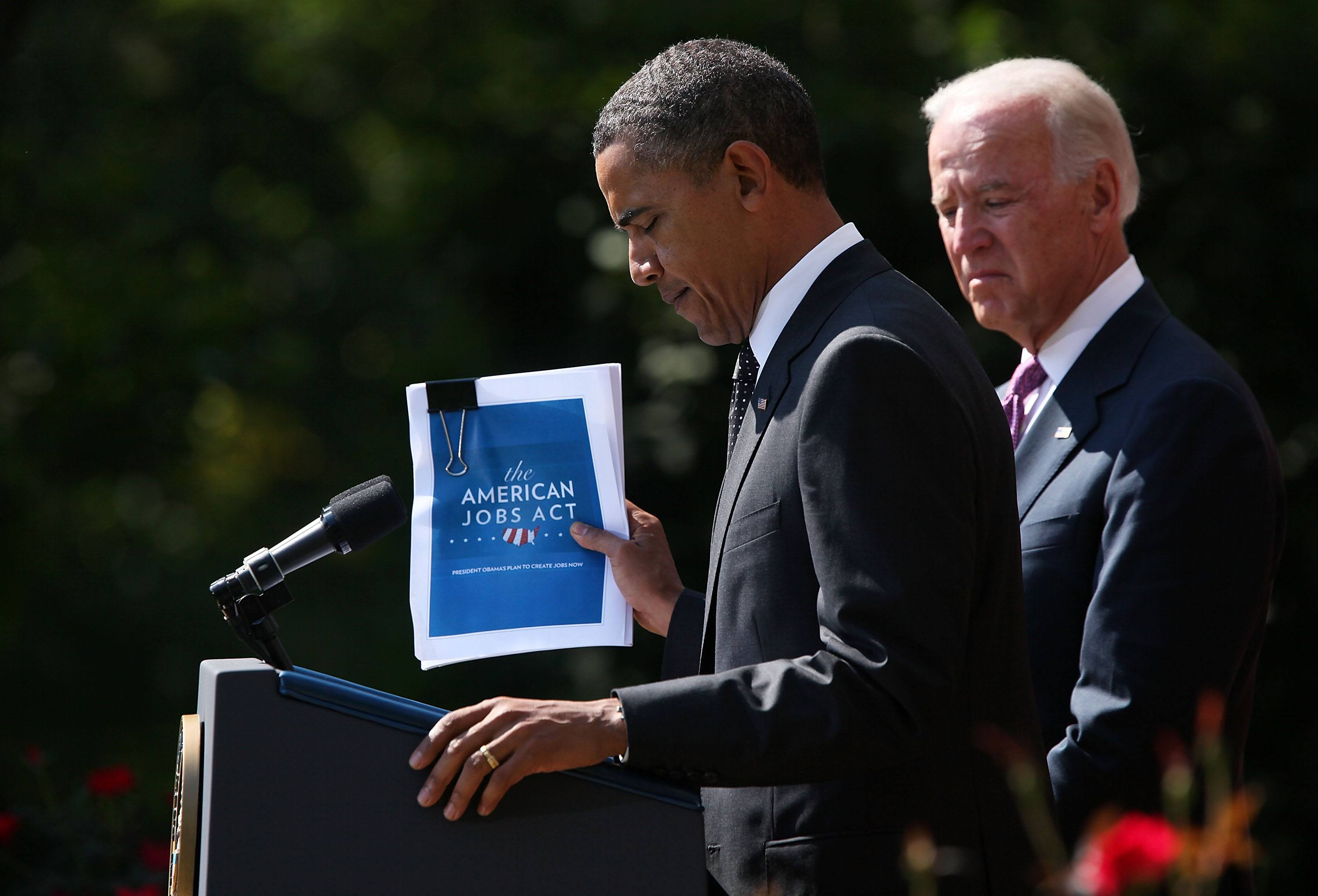 U.S. President Barack Obama holds up a copy of his $400 billion jobs plan he is sending to Congress as Vice President Joseph Biden stands next to him