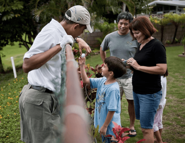 Barack Obama interacting with a family on a golf course.