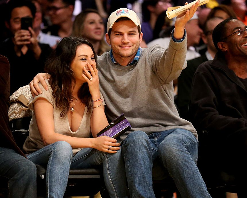 Actors Ashton Kucher and Mila Kunis react after being shown on the video board