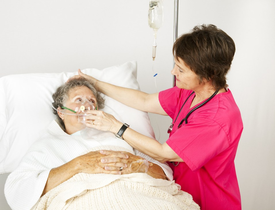 Hospital nurse helps a senior woman breath through an oxygen mask