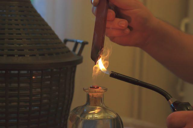 A person melts wax into a container.