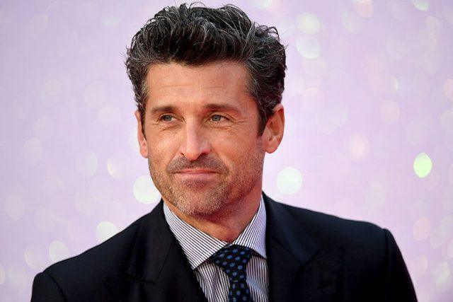 Patrick Dempsey in a suit and tie behind a purple background.