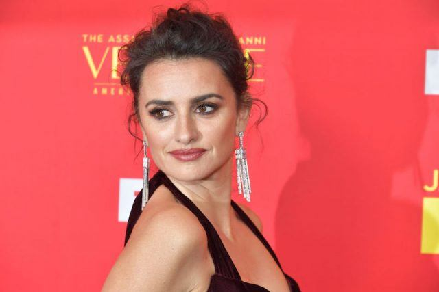 Penelope Cruz posing on a red carpet in a black dress and silver earrings.