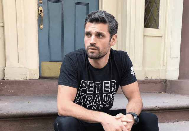 Peter sits on steps in front of a building.