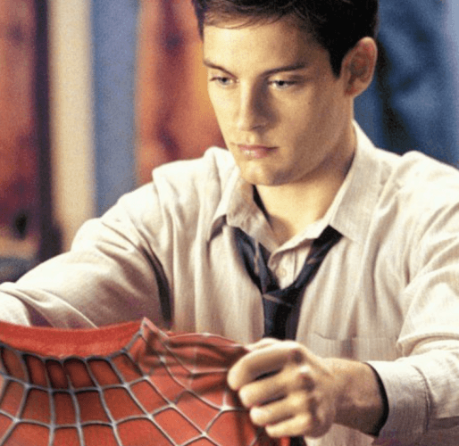 Peter Parker holding up his suit.