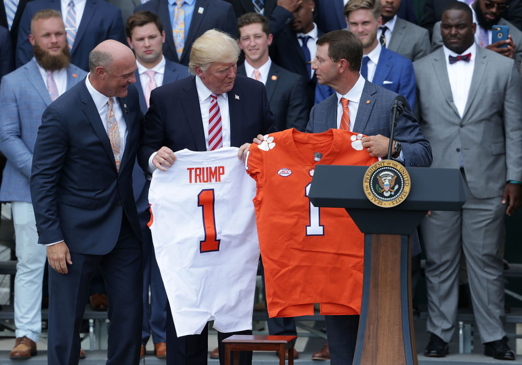 Clemson University President Jim Clements (L) and Clemson Tigers head coach Dabo Swinney (R) present two jerseys, one for President Donald Trump