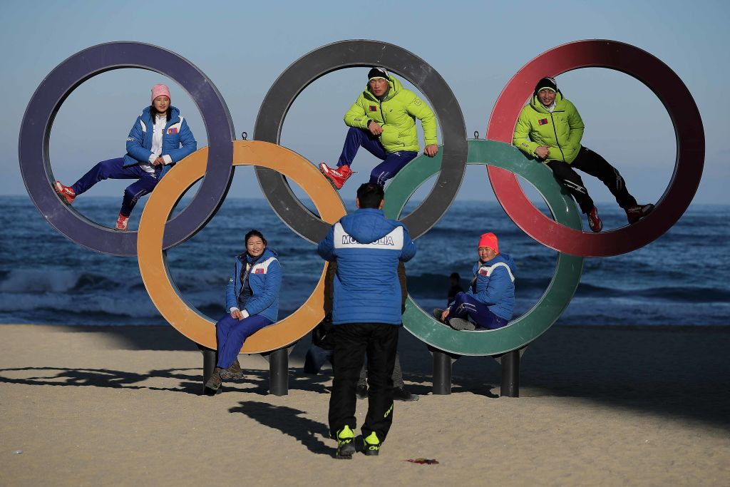 Members of the Mongolian ski team take selfies with the Olympic Rings on the beach at Gangneung