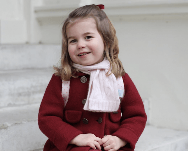 Princess Charlotte sitting on steps wearing a red coat.