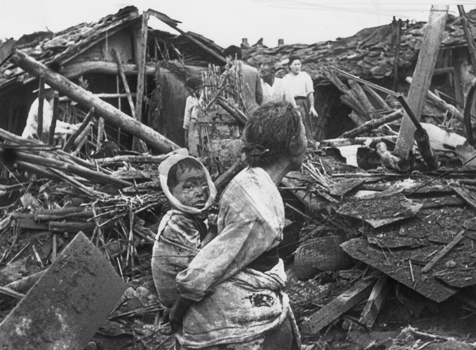 An elderly woman and her grandchild wander among the debris of their wrecked home in the aftermath of an air raid by U.S. planes