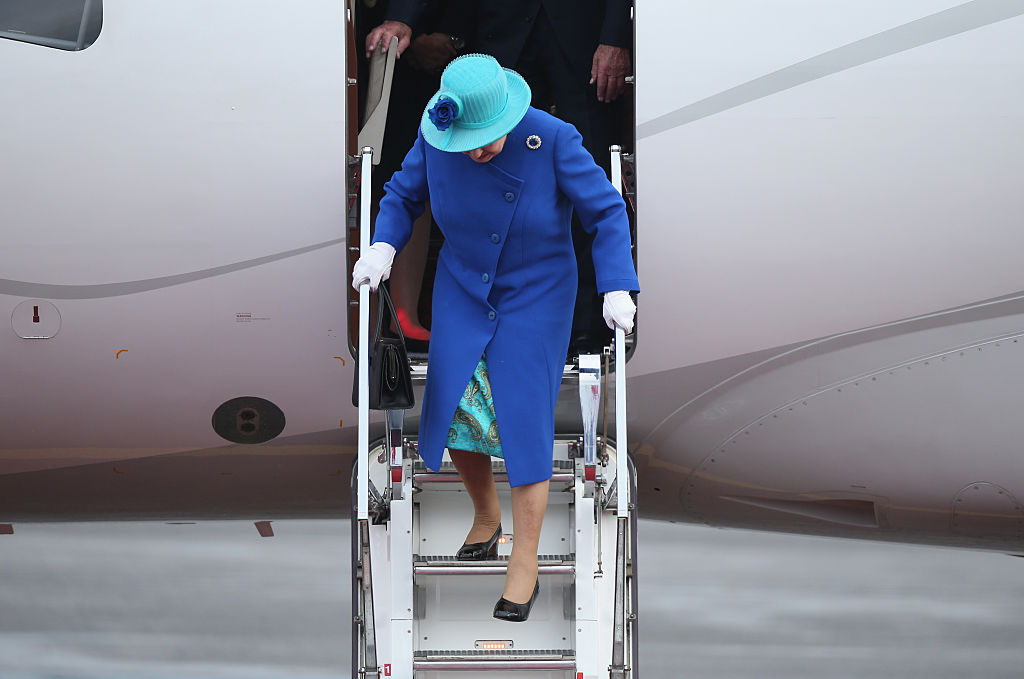 Queen Elizabeth II walks down the stairs of her plane upon her arrival with Prince Philip, the Duke of Edinburgh, at Tegel airport