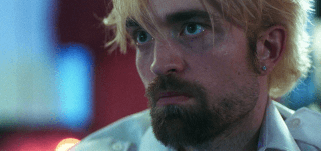 Robert Pattison staring straight ahead in shock in 'Good Time'.