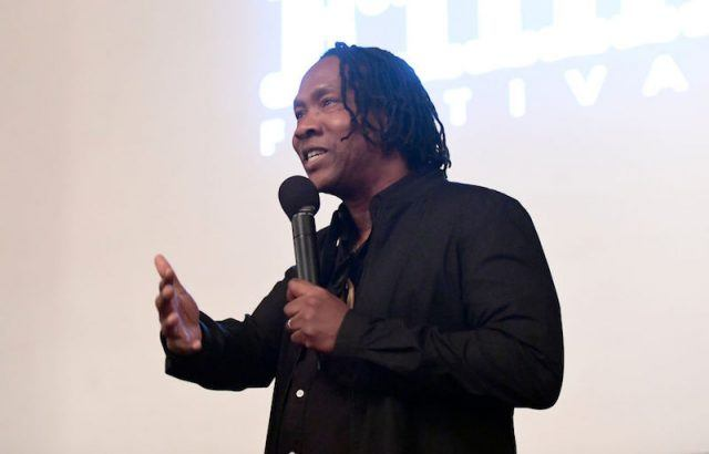 Roger Ross Williams holding a microphone as he speaks on a stage.