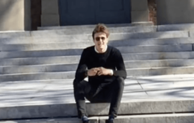 Rory smiles as he sits on a gray staircase.