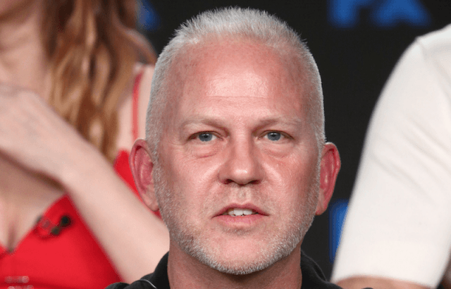 Ryan Murphy sitting on stage during a panel presentation.