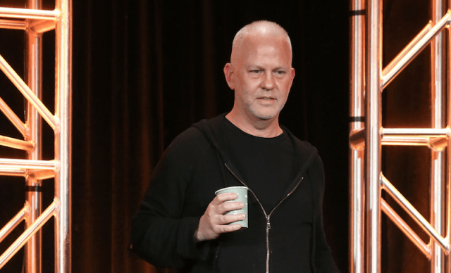 Ryan Murphy walking on stage holding a plastic cup.
