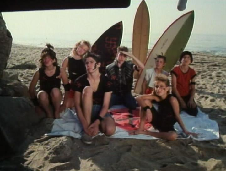 a group of people sits on a towel in the sand with surfboards