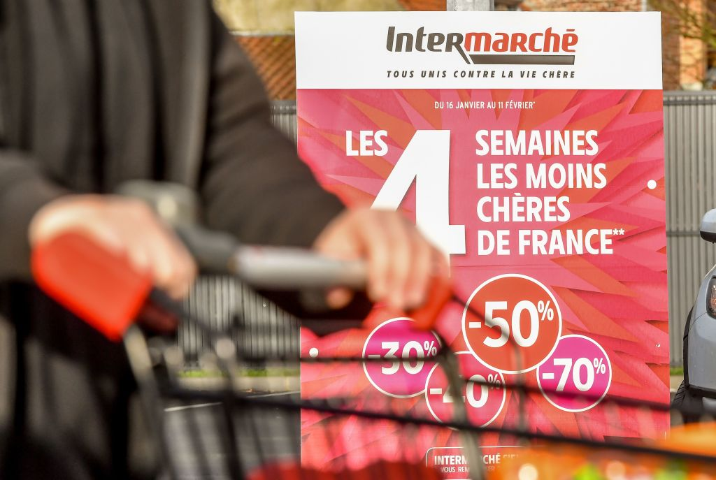 Woman walks past sale sign at Intermarche supermarket