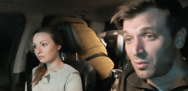 Nia and Sam sitting in their car during a video vlog segment.