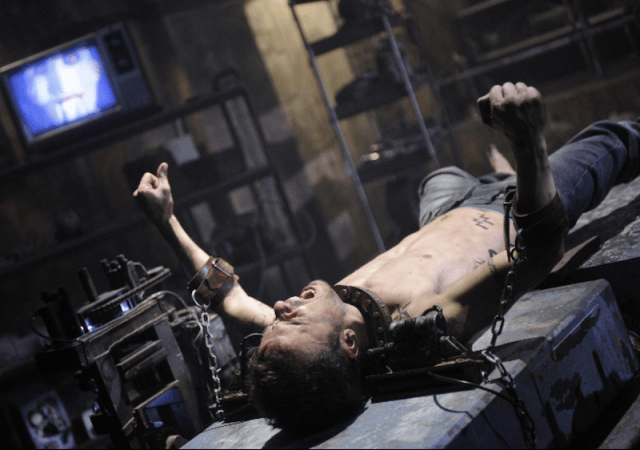 A man is trapped on a table and tied with chains.