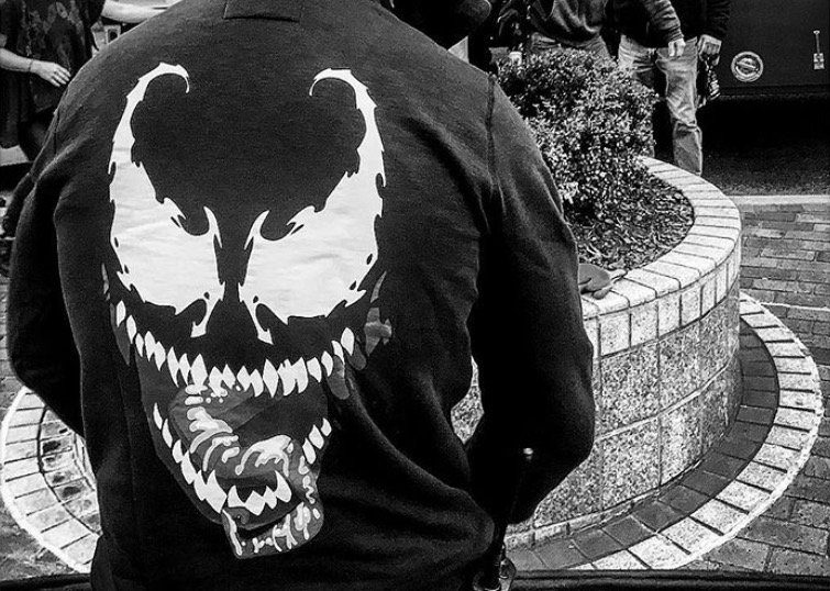 Tom Hardy wears a sweatshirt with a venom logo on the back