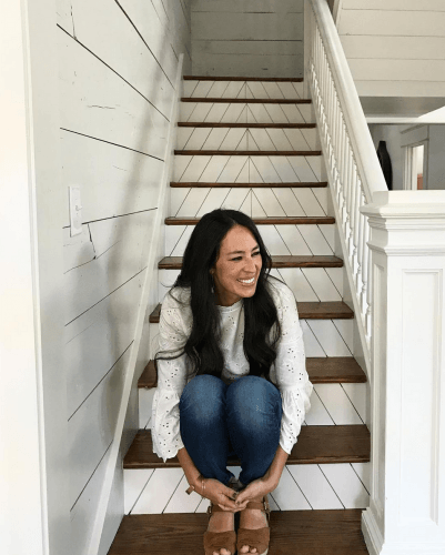 Joanna Gaines sitting on stairs with shiplap walls/
