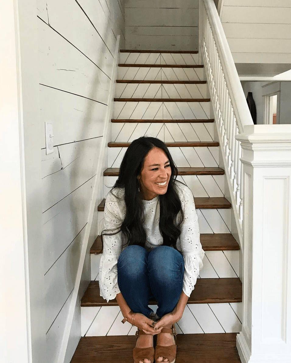 Joanna Gaines sitting on stairs with shiplap walls