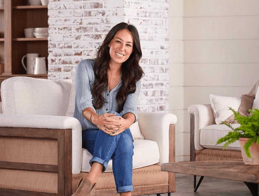 Joanna Gaines sitting in room with shiplap