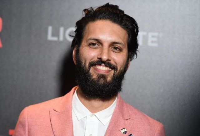 Latif smiles while wearing a salmon colored blazer and white shirt on a red carpet.