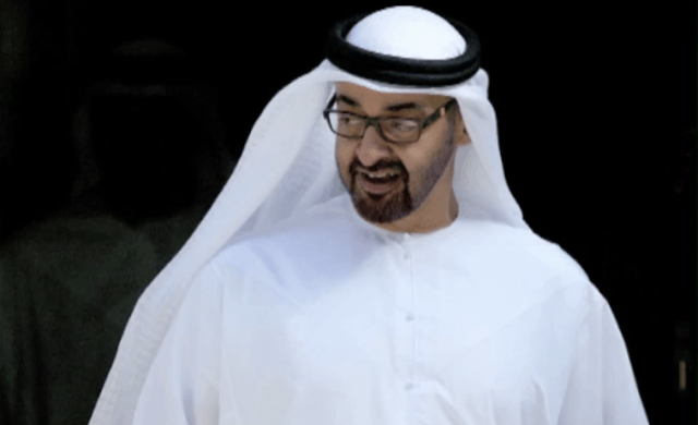 Sheik Mohammed Bin Zayed Al Nahyan stands while greeting guests at an event.