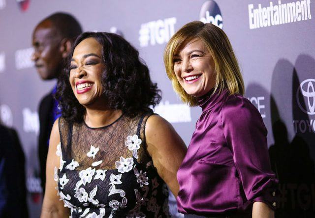 Shonda Rhimes and Ellen Pompeo smiling together on the red carpet.