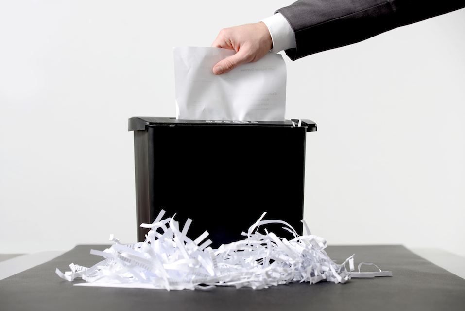 Businessman putting a document in paper shredder
