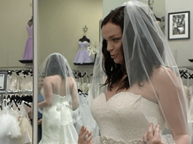 A woman trying on a wedding gown.
