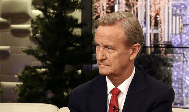 Steve Doocy wearing a black suit and red tie.
