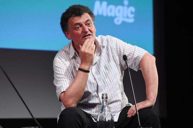 Steven Moffat sitting in front of a microphone on stage.