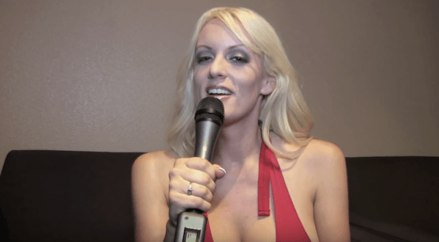 Stormy Daniels sitting on a couch while speaking into a microphone.