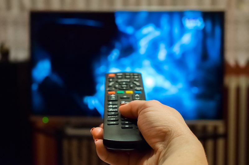 hand pointing remote at TV
