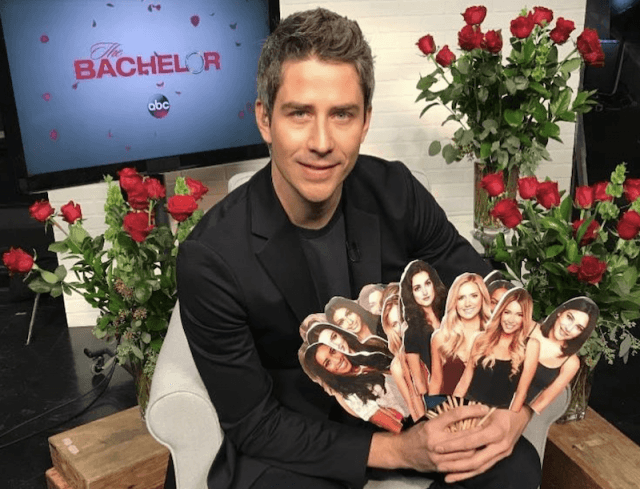 Arie holding up a bouquet of photos of the women in the show.