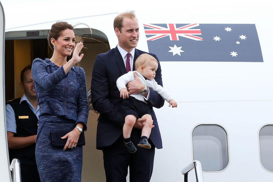 Catherine, Duchess of Cambridge, Prince William, Duke of Cambridge and Prince George of Cambridge wave to the crowd before boarding a Royal Australian Air Force plane