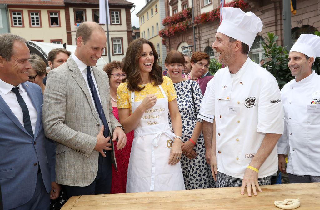 Prince William, Duke of Cambridge and Catherine, Duchess of Cambridge are shown how to make pretzels during a tour of a traditional German market in the Central Square
