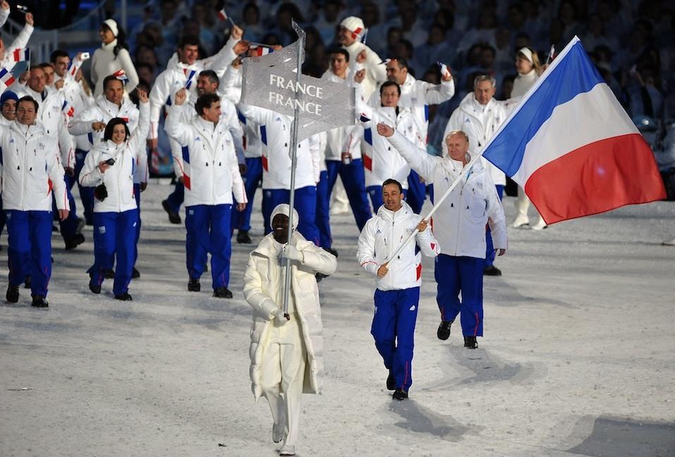 The French delegation, led by flagbearer, biathlon athlete Vincent Defrasne, enter the stadium