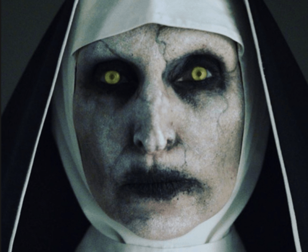 Nun with green eyes and dark makeup.