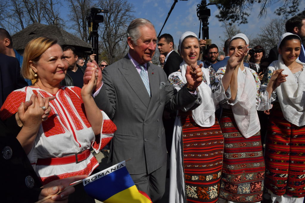 Prince Charles, Prince of Wales dances with Romanian dancers at a village museum on the second day of his nine day European tour