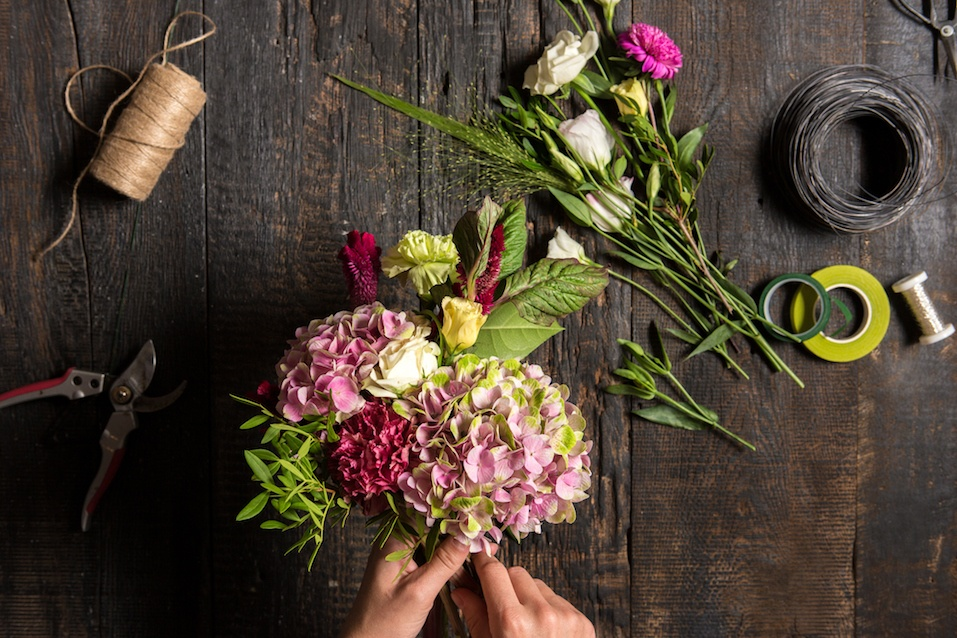 The hands of florist against desktop with working tools and ribbons