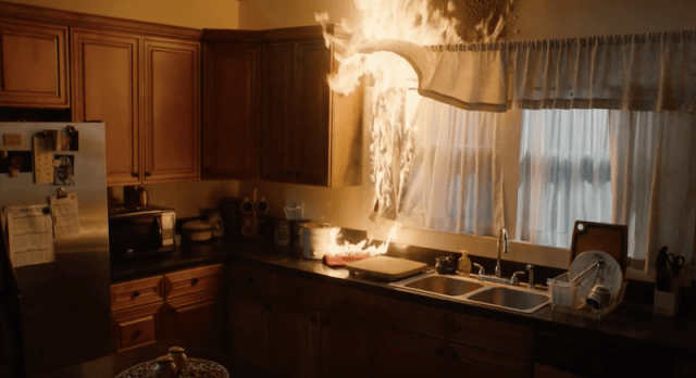 A curtain being caught on fire.
