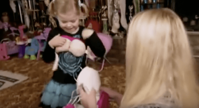 A young girl tries on a costume.