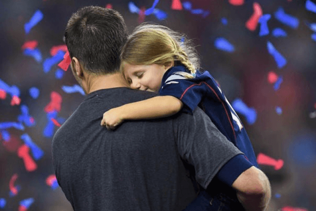 Tom Brady holding his daughter.
