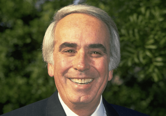 Tom Snyder smiling in front of trees.