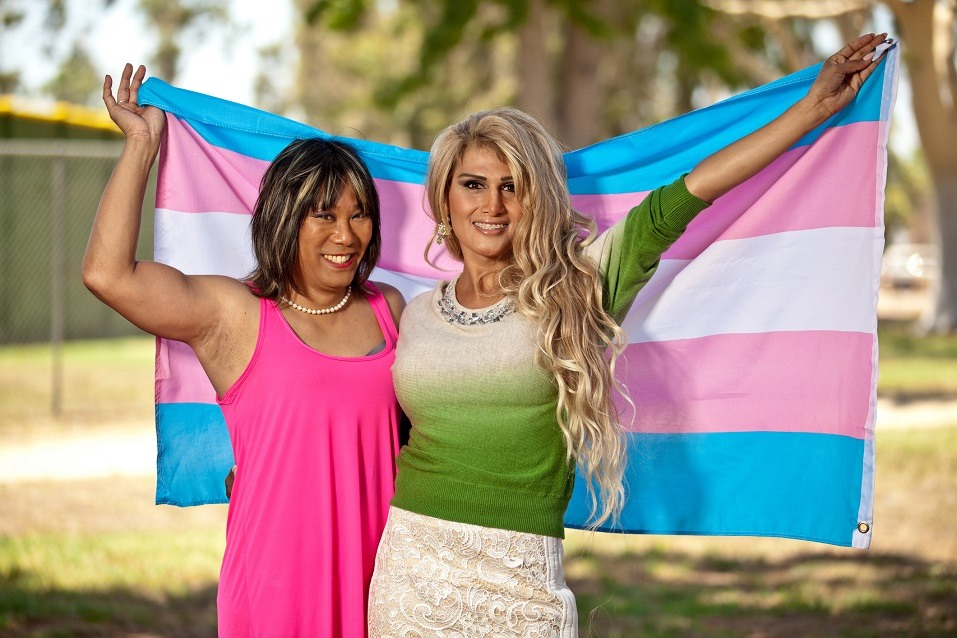 Transgender females holding Pride flag behind them