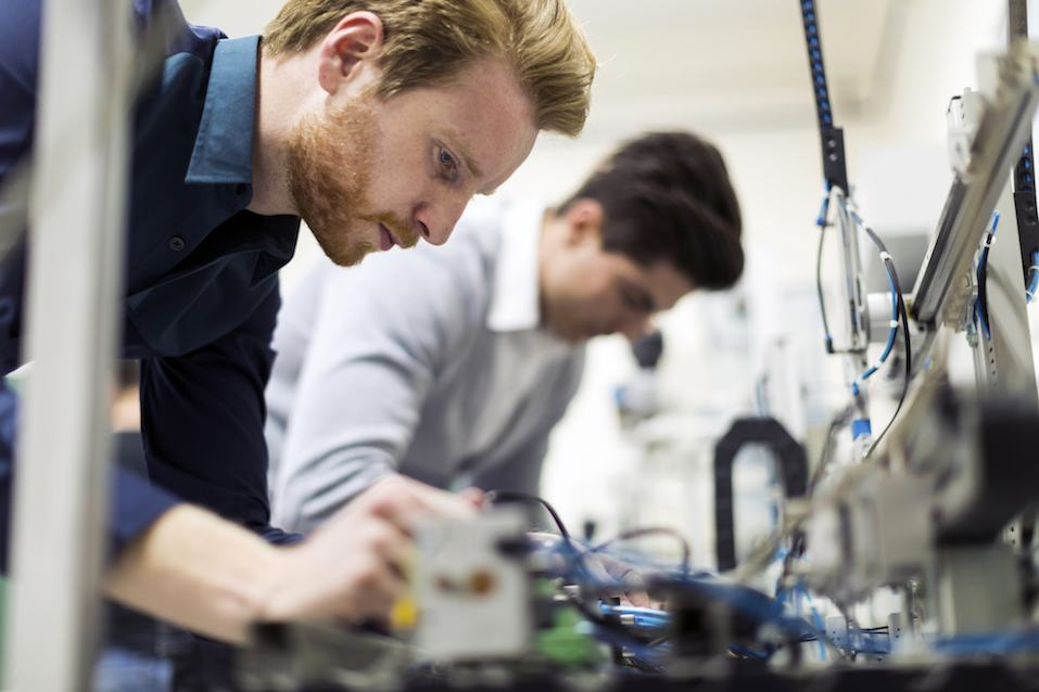 Engineers working on electronics components and fixing broken chips